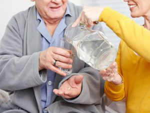 Old man at home taking a pill with glass of water